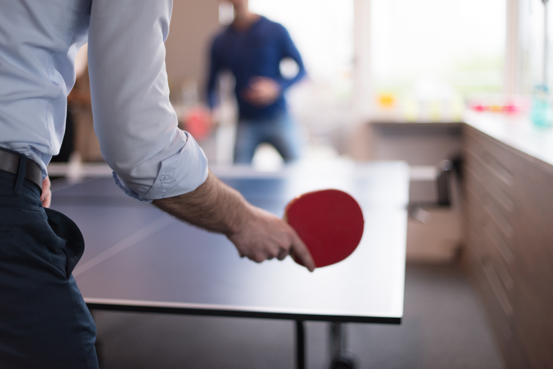 Two professionals playing ping pong in their office