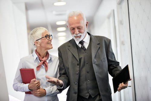 Elderly business people talking and walking down office hallway